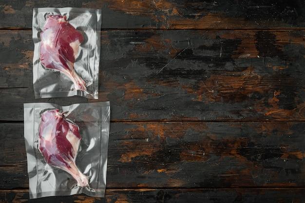 真空調理セット用のシールバッグに入った生のアヒルの脚の肉、古い暗い木製のテーブルテーブル、コピースペース付き