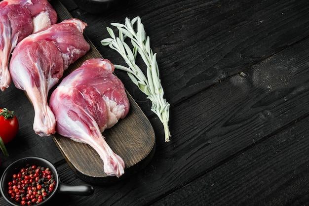 生のアヒルの脚の太もも、ハーブと材料、黒い木製のテーブルテーブル