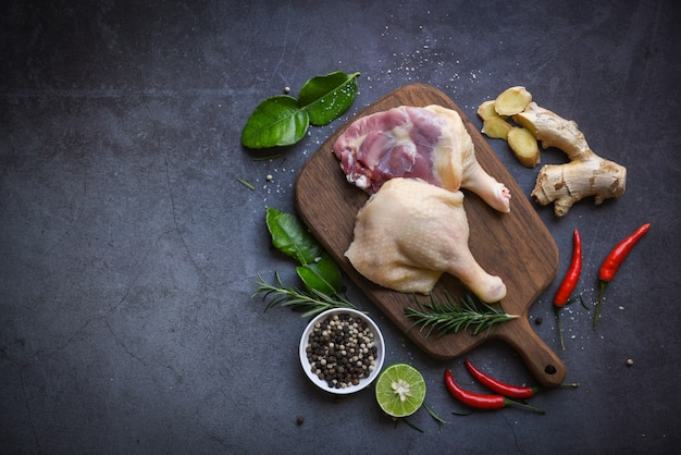 Raw duck legs with herb spices ready to cook on wooden cutting board, fresh duck meat for food