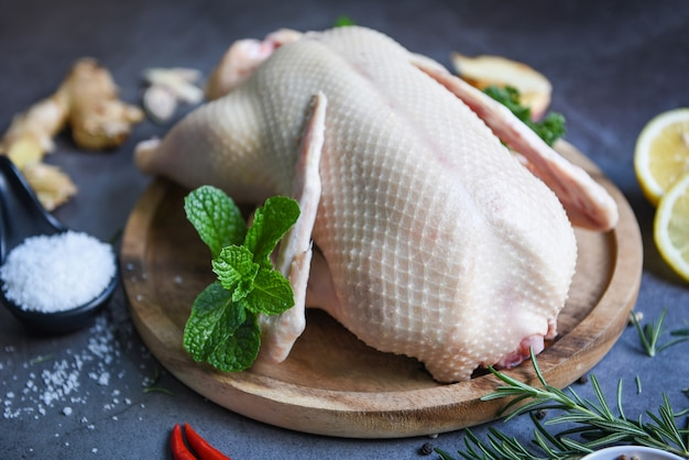Raw duck with herb spices ready to cook, fresh duck meat on wooden tray for food, whole duck