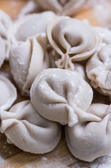 Raw dumpling on bamboo wickerwork with flour and pepper