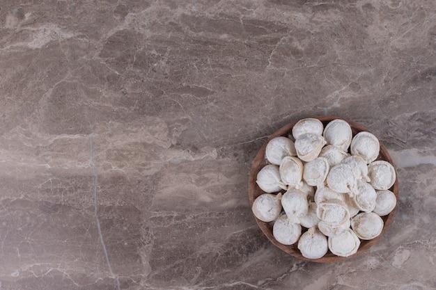 Сырые пельмени на деревянной доске.