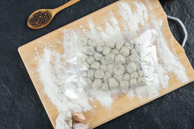 Gnocchi crudi con farina su tavola di legno.