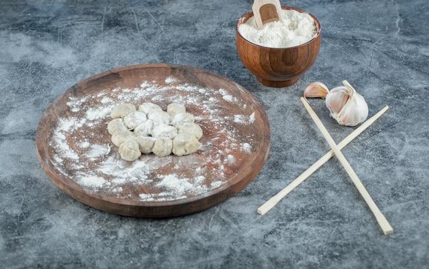 Raw dumplings with flour on wooden board.