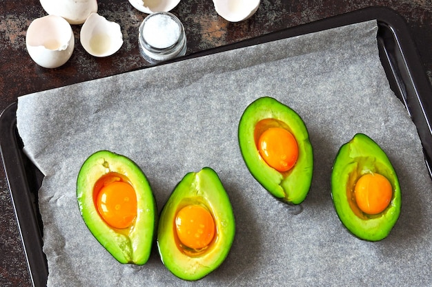 Raw egg in avocado on a baking sheet. cooking avocado with egg. keto lunch recipe.