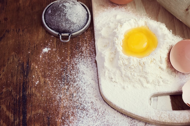 Raw egg in a hill of flour, baking background, space for text