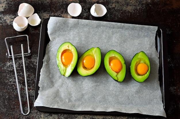 베이킹 시트에 아보카도에서 날 달걀입니다. 계란으로 아보카도 요리. 케토 점심 레시피.