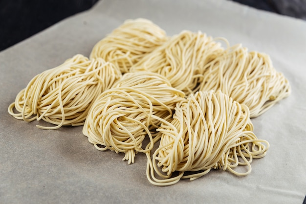 Raw egg noodle nests on the parchment paper