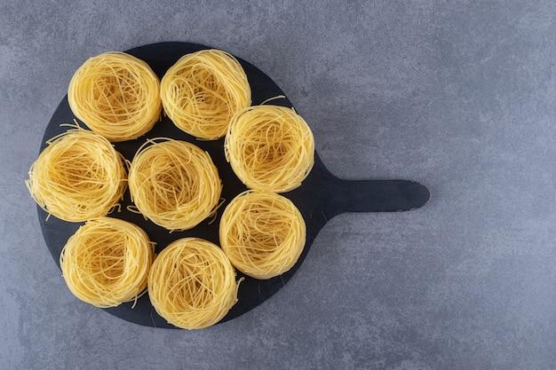 Raw egg noodles on black board.