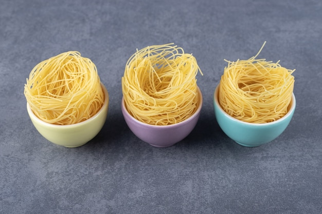 Raw egg noodles in colorful bowls.