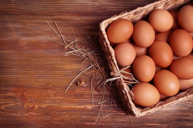 나무 테이블에 바구니에 원시 계란