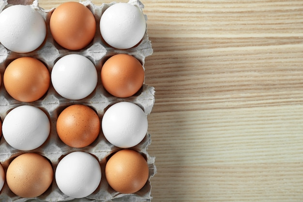 나무 테이블에 패키지에 원시 계란