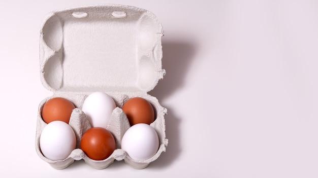 Сырые яйца в переработанной экологической коробке на светлом фоне с копией пространства