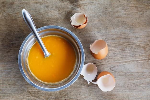 Сырые яйца, перемешанные в миске для приготовления
