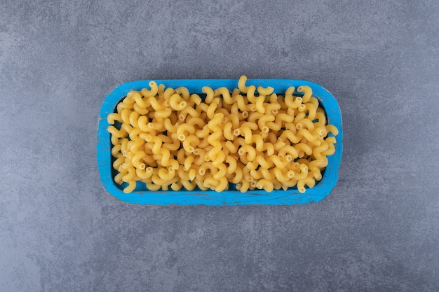 Raw elbow macaroni on blue plate.