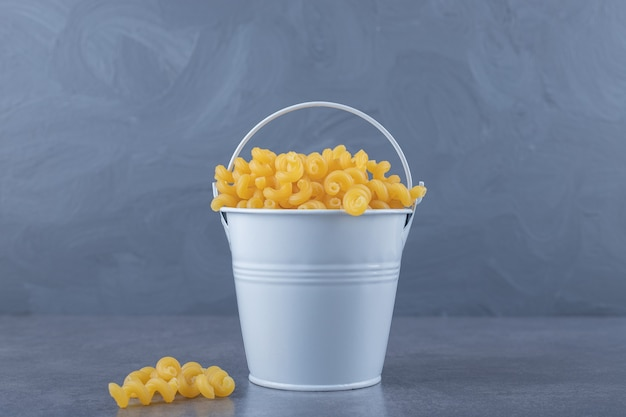 Raw elbow macaroni in metal bucket.