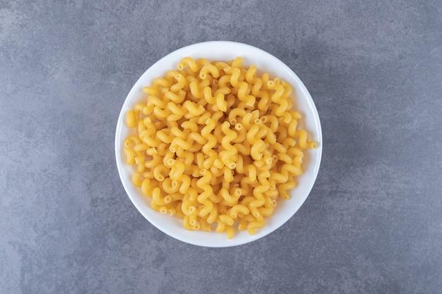 Raw elbow macaroni on white plate.
