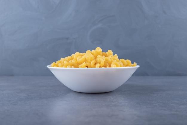 Maccheroni crudi del gomito sul piatto bianco.