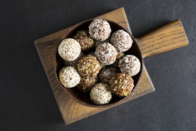 Raw energy balls in the wooden bowl on the board on dark