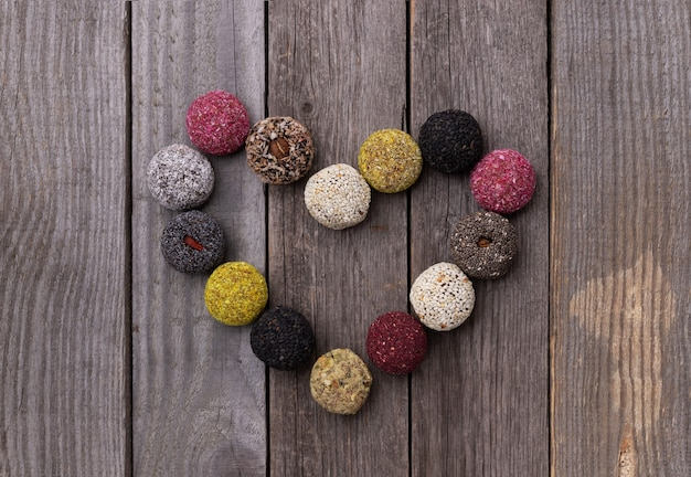 Raw energy bites balls in heart shape on old rustic wooden background.
