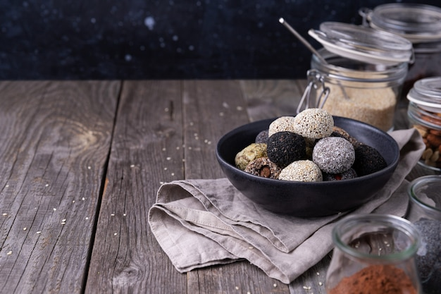 Raw energy bites balls prepared with natural ingredients on wooden background