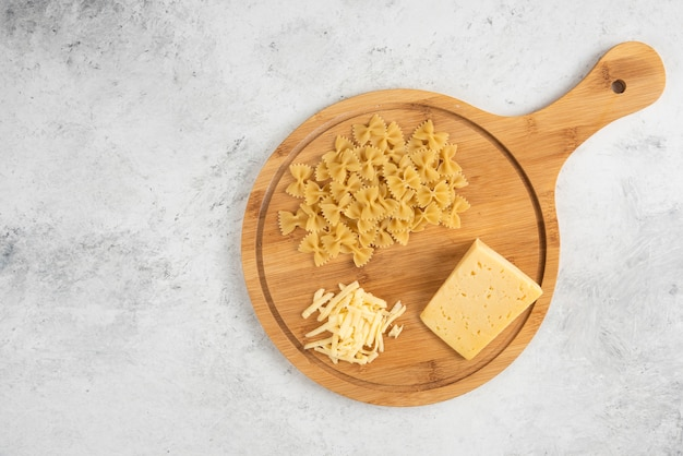 Сырые фарфалле и сырная деревянная доска.
