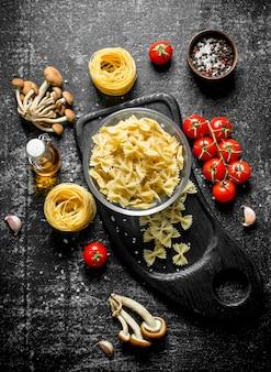 Сырые фарфалле и паста тальятелле в миске на разделочной доске с грибами, помидорами и специями. на деревенском фоне