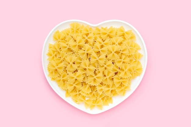 Raw farfalle in a heart shape plate on a pink background, uncooked pasta butterfly or bow tie