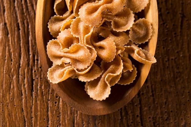 木のスプーンに生のファルファッレまたは蝶ネクタイのパスタ、。木製のテーブルの上の一体型パスタ