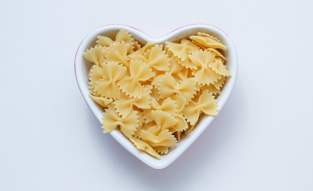 Raw farfalle pasta in a heart shaped bowl on white wall, top view.