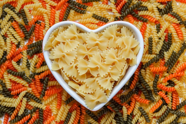 Raw farfalle pasta in a heart shaped plate top view on a colored fusilli table