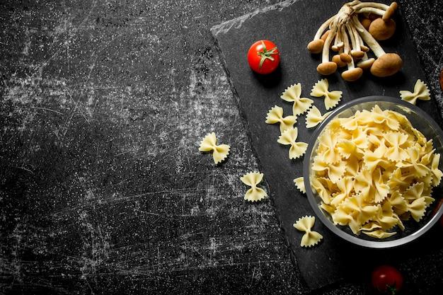 Сырые макароны фарфалле в миске с грибами и помидорами. на черном деревенском фоне