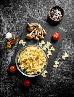 Сырая паста фарфалле в миске с грибами и помидорами на черном деревенском столе