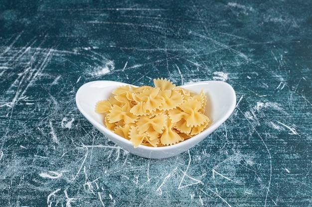 Сырые макаронные изделия фарфалле на белой тарелке. фото высокого качества