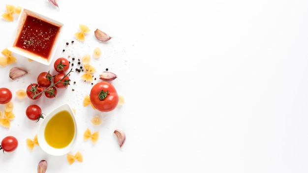 Raw farfalle pasta with tomato; sauce; garlic clove over isolated on white background
