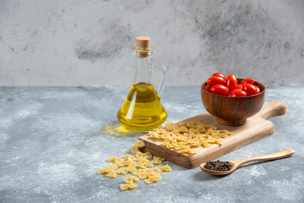 Raw farfalle, tomatoes and olive oil on wooden board.