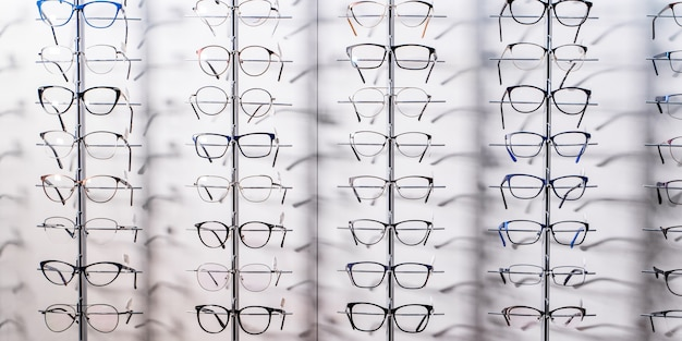 Raw of fashion elegance glasses in the store. showcase with glasses in modern ophthalmic store. closeup.