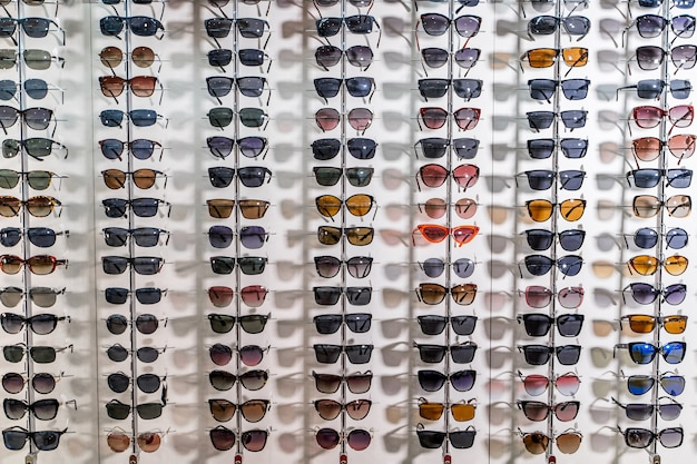 Raw of fashion elegance sunglasses in the store. showcase with sunglasses in modern ophthalmic store. closeup.