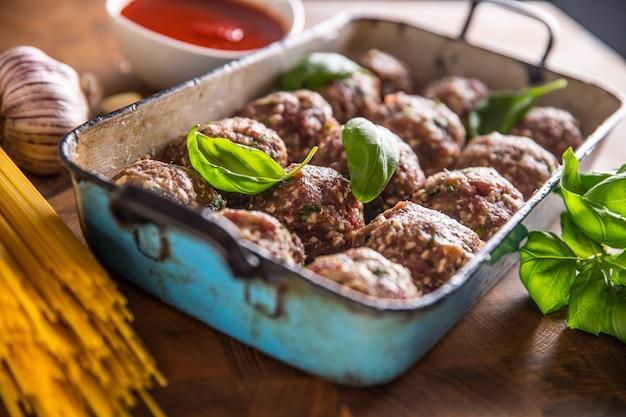 Сырые фрикадельки с базиликом, томатным соусом, чесноком и спагетти на мясной доске.