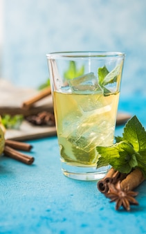 Raw fermented homemade alcoholic or non alcogolic kombucha superfood. ice tea with healthy natural probiotic in glass with mint on  blue background