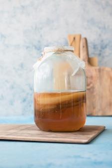 生の発酵自家製アルコールまたは非アルコール昆布茶スーパーフード。青い背景にミントとガラスの健康的な天然プロバイオティクスとアイスティー