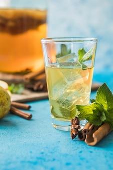 Сырой ферментированный домашний алкогольный или неалкогольный суперпродукт из чайного гриба. холодный чай со здоровым натуральным пробиотиком в стакане с мятой на синем фоне