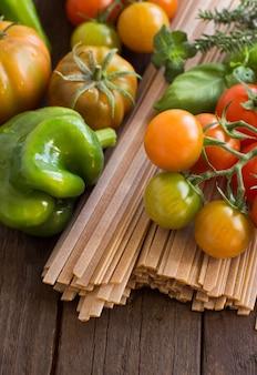 Сырые макароны феттучче, овощи и зелень на дереве крупным планом