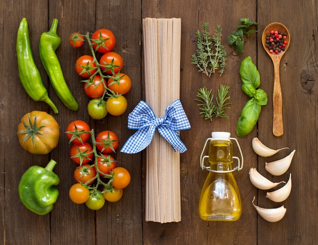 Сырые макароны феттучче, овощи, зелень и оливковое масло на дереве сверху