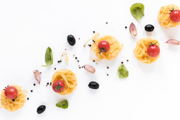 Raw fettuccine pasta; cherry tomato; black olive; garlic clove and basil leaves isolated over white background