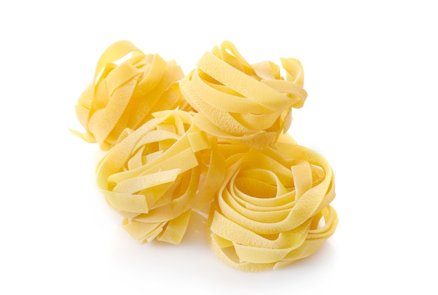 Raw fettuccine pasta isolated on white.
