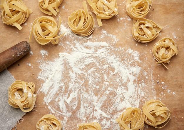 白い小麦粉と茶色の木の板に生のフェットチーネパスタ