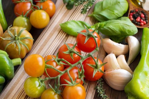 Сырые макароны фетучини, овощи и зелень на дереве крупным планом