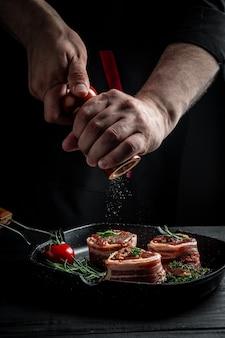 Стейк из сырого филе «миньон», покрытый беконом на сковороде, приготовление мяса на гриле. приготовление стейка из говядины руками шеф-повара. стейки медальоны. баннер, рецепт меню.
