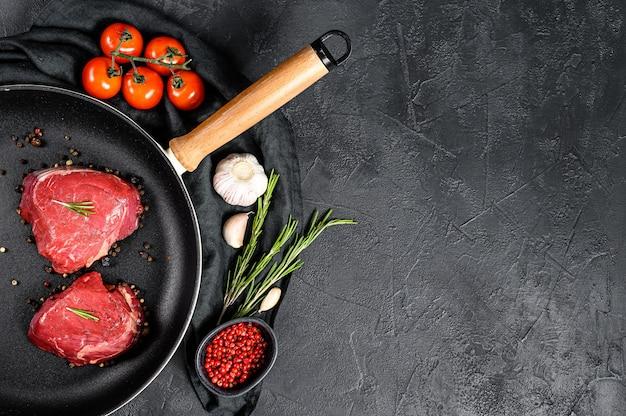 Raw filet mignon steak in a frying pan. beef tenderloin. top view.